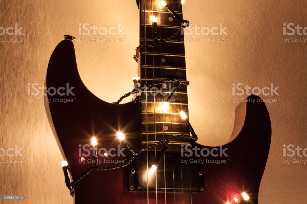 Guitar riff highlighted by new year lights in front of white background stock photo