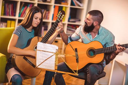 istock Guitar teacher teaching the girl at home. 1055457536