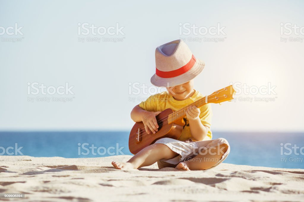 Guitar ukulele concept with little boy at the beach stock photo