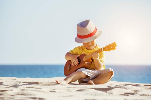 gitarre-ukulele-konzept mit kleinen jungen am strand - ukulele songs stock-fotos und bilder