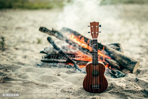 istock guitar ukulele on sand beach. bomifire on the backgraunf 928003446