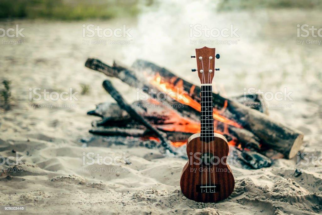 guitar ukulele on sand beach. bomifire on the backgraunf stock photo