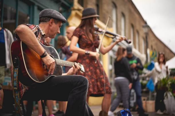 ein gitarrist und ein geiger an der columbia road flower market (london) durchführen. - editorial stock-fotos und bilder