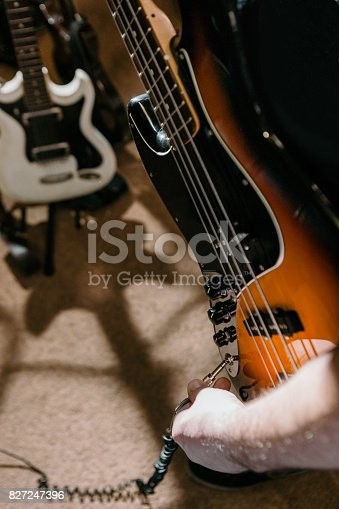 849362192 istock photo Guitarist connecting bass guitar in studio 827247396