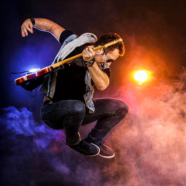 guitarist jumping on stage - popular music concert stock photos and pictures