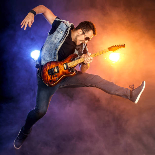 guitarist jumping on stage - rock musician stock pictures, royalty-free photos & images