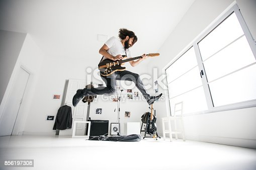 Young man jumping while playing electric guitar. Guitar head is changed, and it's not a copy of any existing guitar. Guitar head does not look like any other existing guitar head.