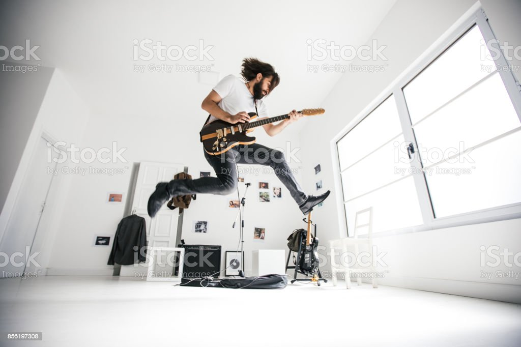 Guitarist jumping stock photo