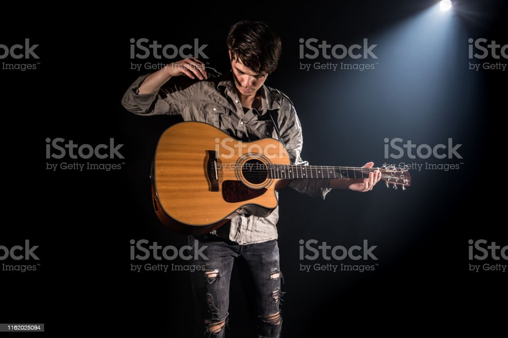 Guitarist, music. A young man plays an acoustic guitar on a black...