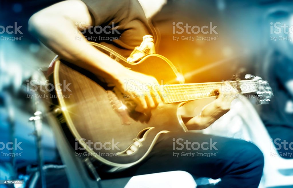 Guitarist on stage for background, vibrant soft and motion blur stock photo