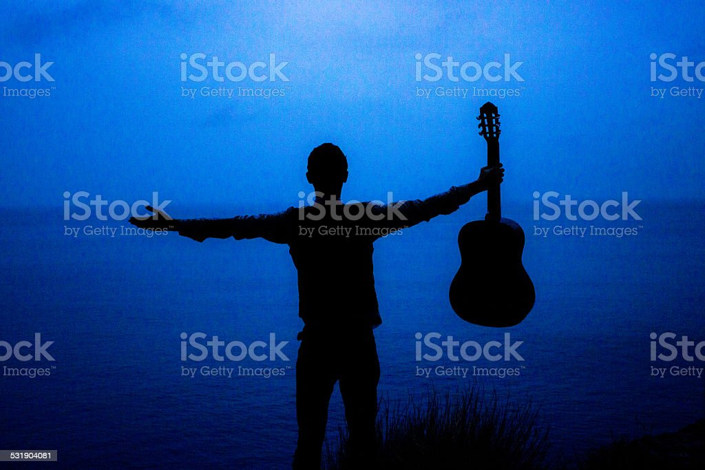 Guitarist opening his arms against nature with his guitar stock photo