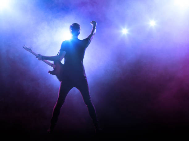 Guitarist performing on stage Silhouette of guitar player on stage on blue background with smoke and spotlights guitarist stock pictures, royalty-free photos & images