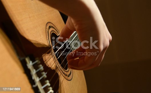 There is a woman who playing the classic guitar.