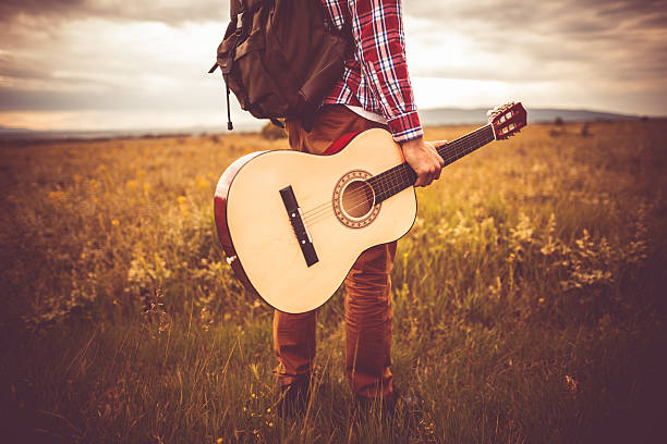 Guitarist Photo of young man in nature with guitar folk music stock pictures, royalty-free photos & images