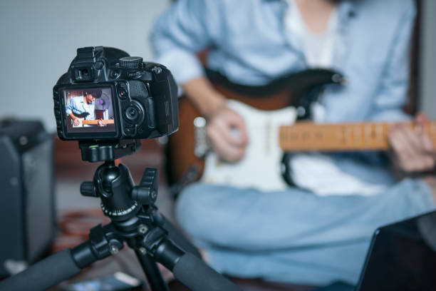 Guitarist recording a video of himself while playing an electric guitar in bedroom studio stock photo