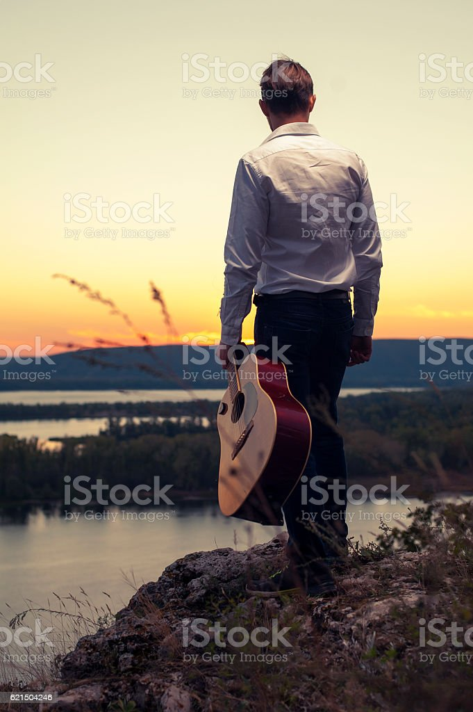 Guitarist standing back on the coast foto stock royalty-free