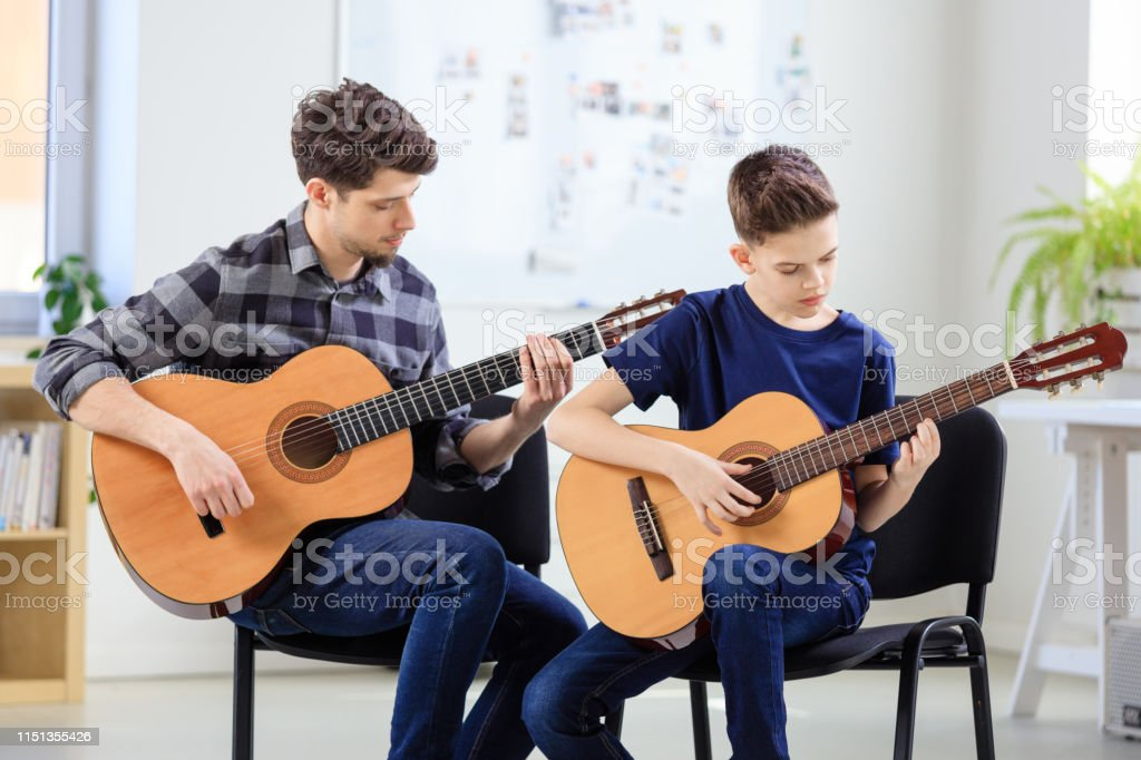 Guitarist teaching boy plucking string instrument Guitarist teaching boy plucking string instrument at classroom. Males are practicing guitar at conservatory. They are in training class. 12-13 Years Stock Photo