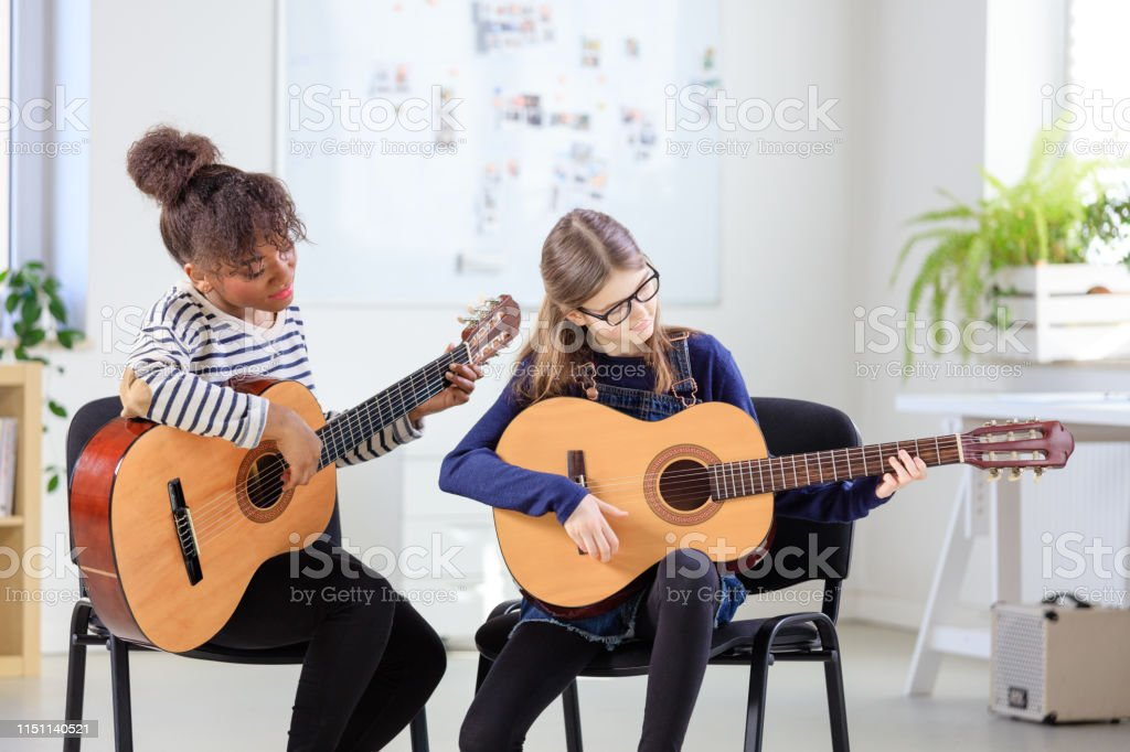 Guitarist teaching female student plucking guitar Female guitarist looking at student plucking guitar. Pre-adolescent girl is learning musical string instrument from teacher. They are in training class at conservatory. 10-11 Years Stock Photo