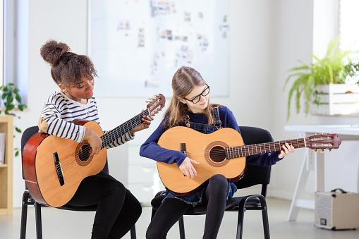 Guitarist Teaching Female Student Plucking Guitar Stock Photo - Download Image Now