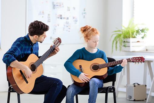 Guitarist Teaching Student Plucking Guitar Stock Photo - Download Image Now