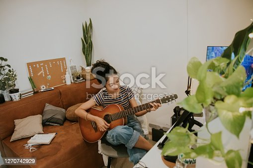 Thai artist woman freelancer just relaxing while playing guitar after work at home, Bangkok Thailand