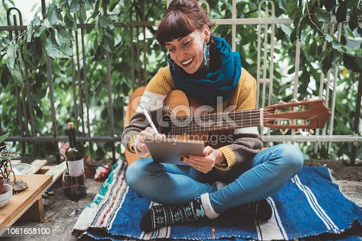 Young woman sitting at the terrace and using tablet to create new music