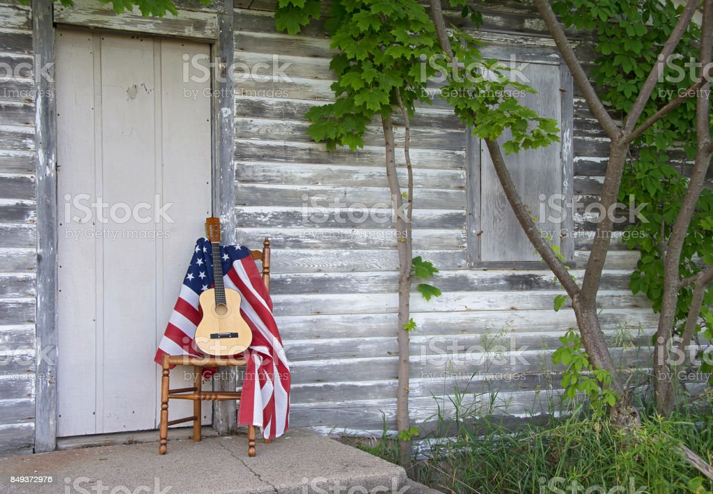 guitars and American flag on chair by door stock photo