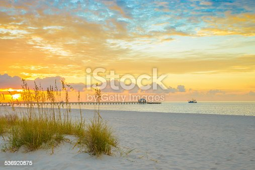 Gulfport Mississippi beach, dramtic golden sunrise, pier, shrimp boat, on the Gulf of Mexico