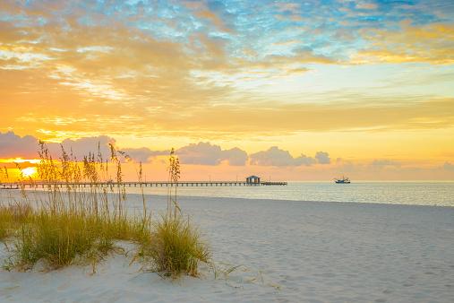 Gulfport Mississippi beach, dramtic golden sunrise, pier, shrimp boat, bay