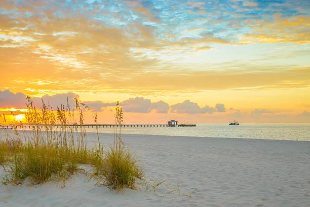 Gulfport Mississippi beach, dramtic golden sunrise, pier, shrimp boat, bay stock photo