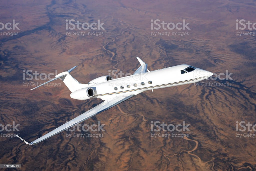 Gulfstream jet flying over desert landscape stock photo