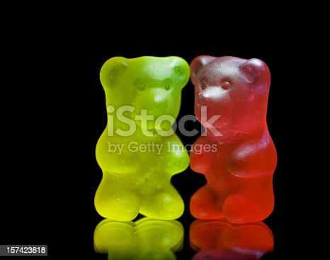istock Gummy bear couple close up isolated on black 157423618