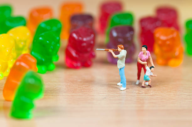 gummy bear invasion. junk food concept - figurine stock photos and pictures