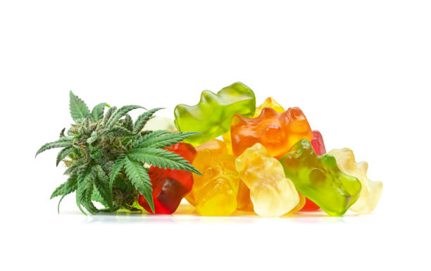 Gummy Bear Medical Marijuana Edibles (CBD or THC Candies) with Cannabis Bud Isolated on White Background stock photo