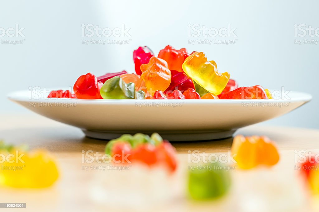 gummy bears on a white plate and wooden table stock photo