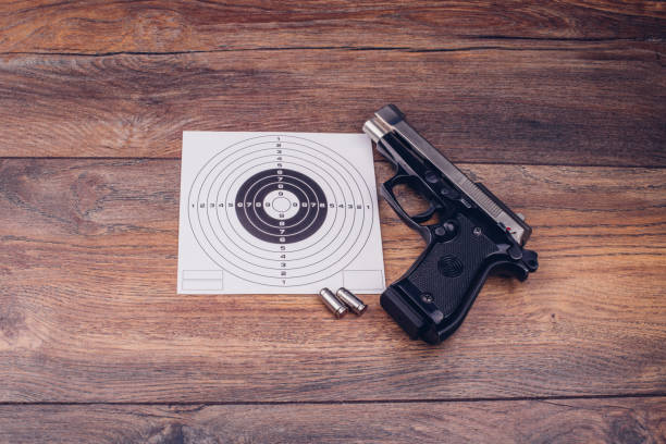 Gun and bullets next on a target sign on a wooden table stock photo