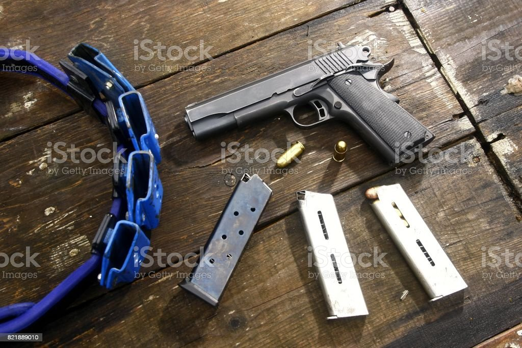 Gun and bullets on a table stock photo