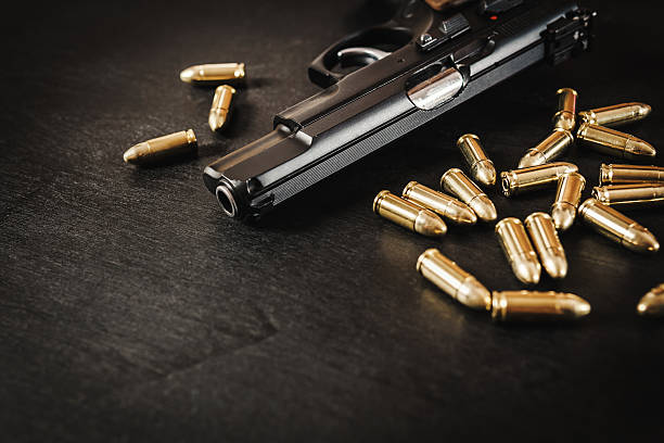 gun and bullets on the table black pistol and cartridges on a black wooden table pistol stock pictures, royalty-free photos & images