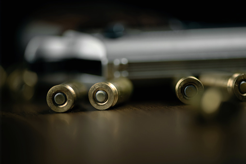 Gun and bullets on wood background