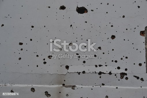 istock Gun bullet-riddle hole on the wall 820959974