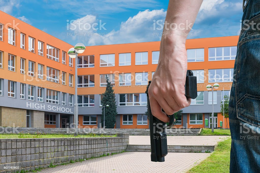 Gun control concept. Young armed man holds pistol in hand. stock photo