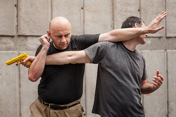 Gun Disarm. Self defense techniques against a gun point. – Foto