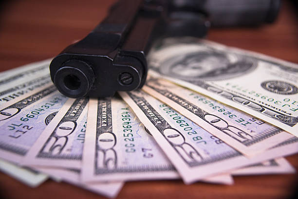 Gun, drugs and money on wooden background stock photo
