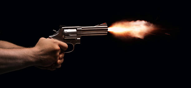 Gun Fire A revolver held by two anonymous hands is fired on a black background. pistol stock pictures, royalty-free photos & images