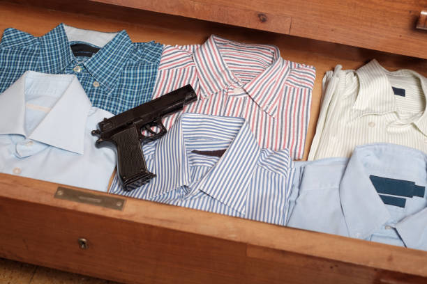 Gun hidden in  drawer full of shirt at home stock photo