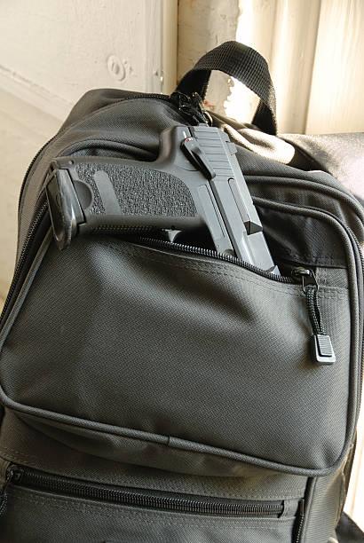 Gun in Bookbag stock photo