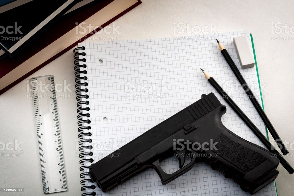 Gun in school next to a notebook, pencils and books Gun control legislation and school shooting prevention concept with a gun on a notebook surrounded by school supplies and copy space Activist Stock Photo