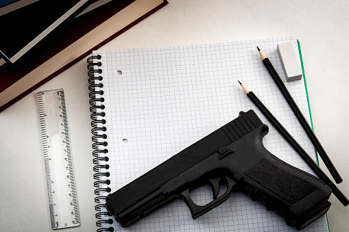 Gun In School Next To A Notebook Pencils And Books Stock Photo - Download Image Now