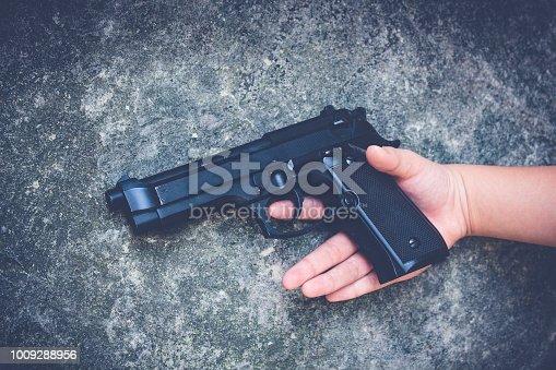 istock Gun in the hands of a children. 1009288956