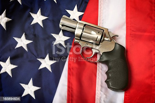 A handgun resting on an American flag, representing the Second Amendment of the US Constitution, the right of patriotic Americans to bear arms. Social issues concept.